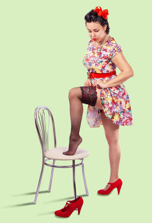 young woman straightens her stocking by placing her leg on the chair. pinup style Standard-Bild