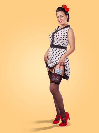 young pretty smiling woman in white dress, black stockings and red shoes standing in studio. pinup style