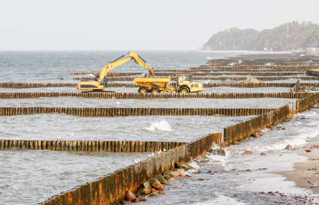 excavator during the construction of a breakwater by the sea on autumn day Standard-Bild