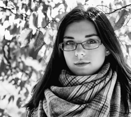 portrait of a young beautiful girl in brown jacket in city park on sunny autumn day. black and white