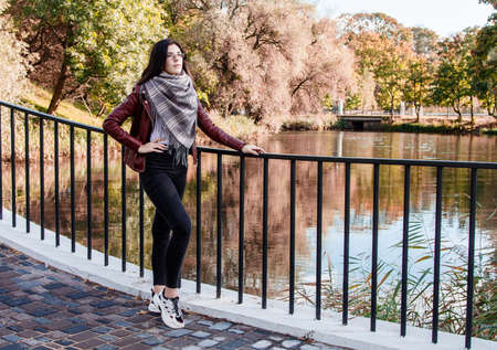 young girl in brown jacket and black jeans standing on bridge near the river in city park on sunny autumn day