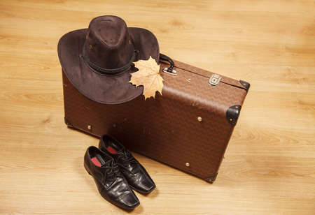 set of men's felt hat with a yellow maple leaf, black shoes and a suitcase on a wooden floor