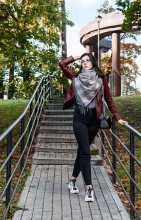 young girl in brown jacket and black jeans standing on the stairs in city park on sunny autumn day Standard-Bild
