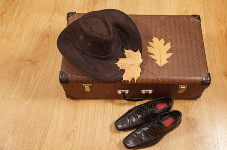 set of men's felt hat with a yellow maple leaves, black shoes and a suitcase on a wooden floor Standard-Bild