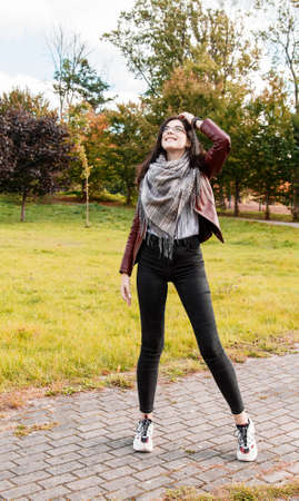 young girl in brown jacket and black jeans standing on the alley in city park on sunny autumn day Standard-Bild
