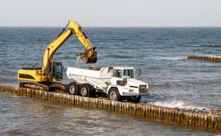 excavator loading soil into a large truck during the construction of a breakwater on the seashore on autumn day Standard-Bild