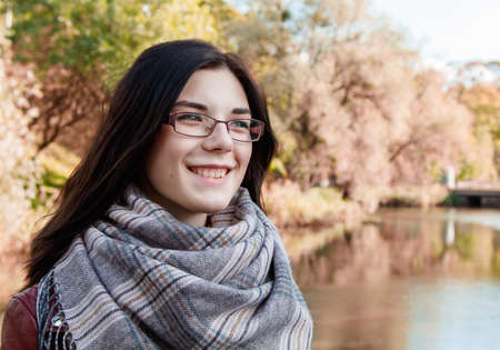 portrait of a young beautiful smiling girl in brown jacket in city park on sunny autumn day
