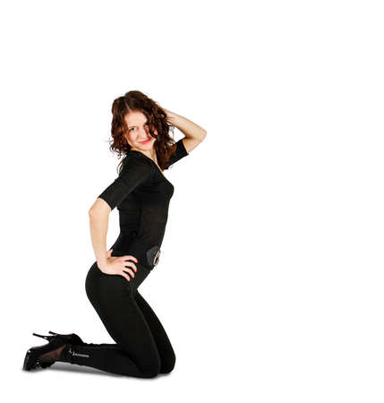 young beautiful woman in black suit posing crouching in studio on white background