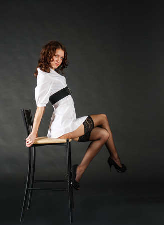 young beautiful woman in white short dress posing while sitting on a chair in the studio