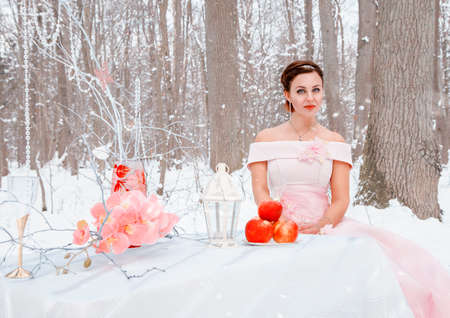young beautiful woman in a pink dress sits at a table in the forest on a winter day