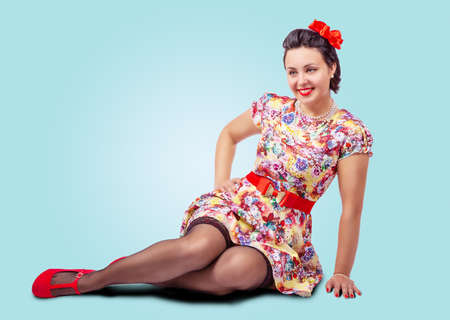 young beautiful woman posing while sitting on the floor in studio. pinup style