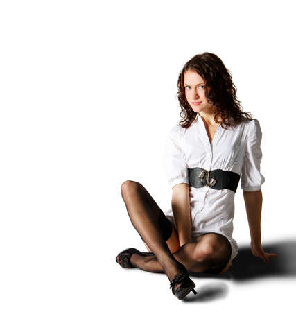 young beautiful woman in white short dress posing sitting on the floor in studio on white background