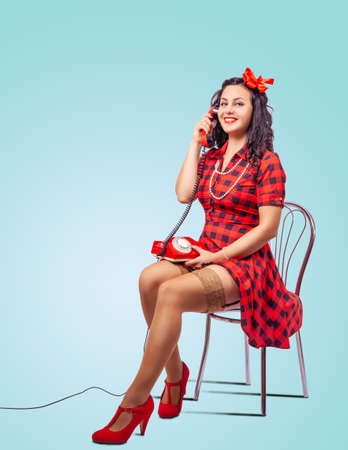 young beautiful woman speaks by phone while sitting on a chair in studio. pinup style Standard-Bild