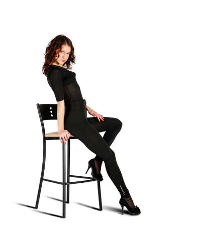 young beautiful woman in black suit posing sitting on a high chair in studio on white background