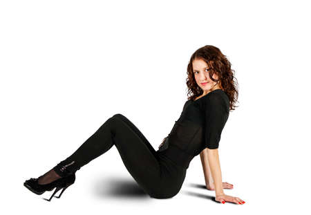 young beautiful woman in black suit posing sitting on the floor in studio on white background