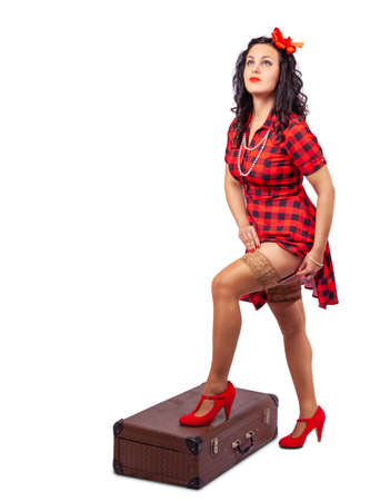 young beautiful woman standing with a suitcase in studio on white background. pinup style