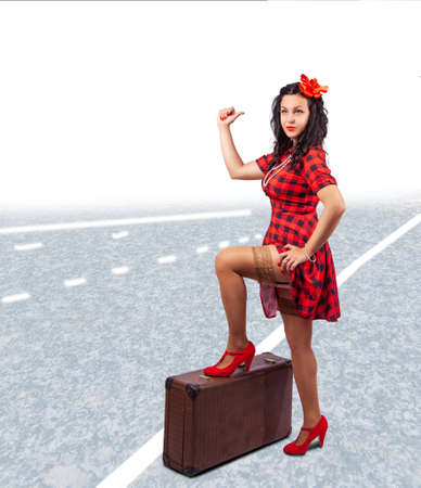young beautiful woman stops the car standing with a suitcase on the road. pinup style