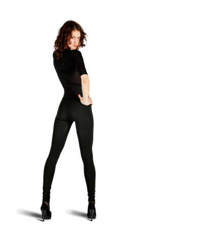 young beautiful woman in black suit posing standing in studio on white background. back view Standard-Bild
