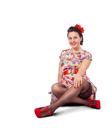 young beautiful woman posing while sitting on the floor in studio on white background. pinup style