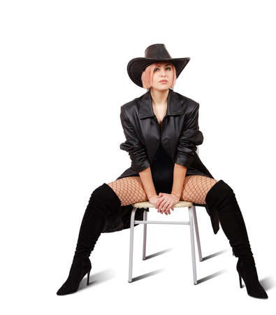 young blonde woman in hat, leather coat, mesh tights and boots posing sitting on chair in studio on white background Standard-Bild