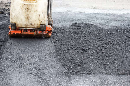worker ramps the asphalt on the road with a mechanical rammer. laying the road surface. hot asphalt under the pressure of the rammer
