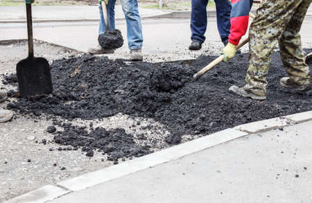 workers laying hot asphalt on the road surface on spring day