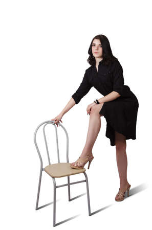 young brunette woman in black dress posing standing with her foot on a chair in studio on white background