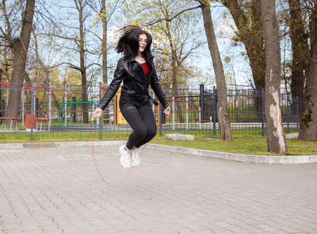 young brunette girl in black jacket and jeans jumping rope outdoor on sunny spring day