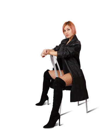 young blonde woman in leather coat, mesh tights and boots posing sitting on chair in studio on white background