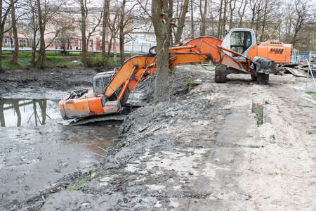 two excavators in the river during renovation on sunny spring day Standard-Bild