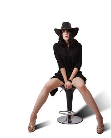 young brunette woman in black dress and hat posing sitting on a chair in studio on white background Standard-Bild