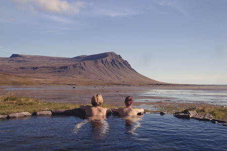 Happy couple in love bathing and relaxing in hot pool with spectacular view of wild landscape Archivio Fotografico