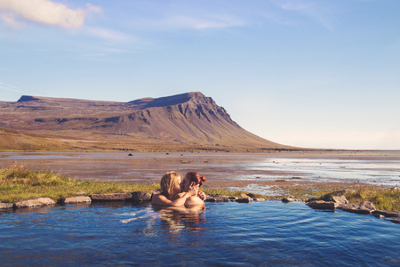 Happy young couple bathing together outdoor- kissing and relaxing in geothermal hot bath in the middle of wild nature in Iceland's West Fjords, Krosslaug pool at Barðastönd Archivio Fotografico