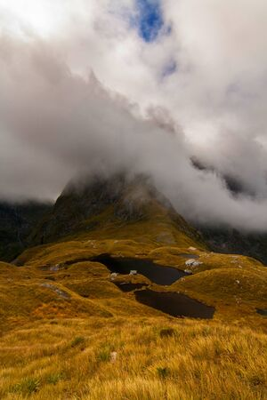 Mountain peak in the dramatic clouds, Milford Track New Zealand, Mackinnon Pass Stock Photo
