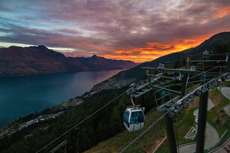 Sunset view of the lake, city and mountains with gondola, Southern Alps, Queenstown Фото со стока