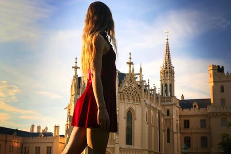 Brown haired girl in red velvet mini dress walking around the castle on sunset, Lednice Castle, Czech Republic