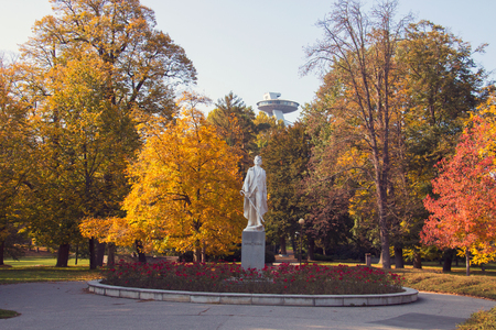 The Janko Kral City Park in Bratislava, autumn leaves on the huge trees and statue of the poet in the centre Stok Fotoğraf