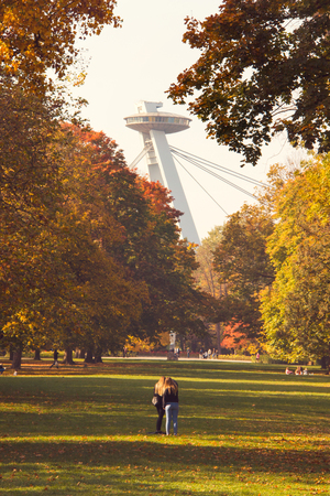 Autumn mood city park view, colourful autumn leaves on the huge trees, statue of Janko Kral in the front and UFO tower bridge architecture on background