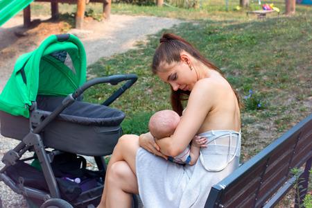 Jonge vrouwen borstvoeding baby, zorgzame moeder zachtjes haar zoontje vast te houden en verpleging in het openbaar, zittend op een bankje, genieten van mooi weer voor wandelwagen wandelen in het park
