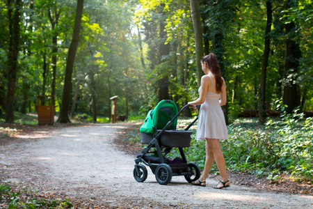 Woman in dress walking with the pram, surrounded by beautiful nature, pram walk on the walkway in the forrest park, parenting mother and baby outside during warm summer day