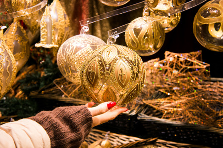 Woman hand holding beautifully crafted Christmas decoration ball in gold colour with ornamental design, traditional vintage Christmas holiday decor, luxury hanging balls displayed on the background