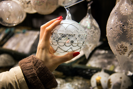 Pretty hand reaching and grabbing Christmas decoration, beautiful ornamental Christmas design, shopping woman hand with long red nails touching luxury silver pearl  Christmas ball displayed in shop