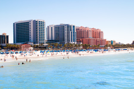 Tropical sandy beach vacation city Clearwater Beach in Florida, colourful beachfront hotel resorts buildings, palm trees, sunbathing tourists, turquoise blue sea waters of Mexican Gulf Stock Photo