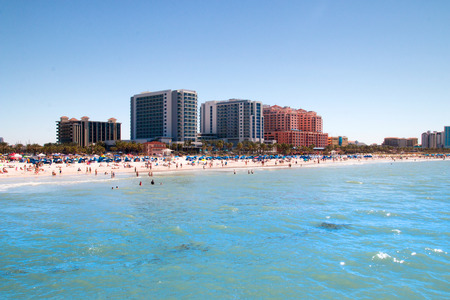 Awesome holidays destination, tropical sandy beach crowded by sunbathing tourists in Clearwater Beach, Florida with holiday resorts and beachfront hotels architecture Stock Photo