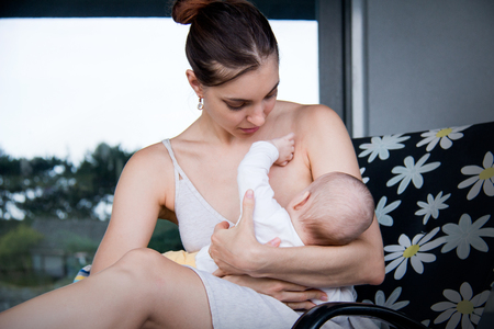 Young caring mother of a baby breastfeeding her little one and sitting on deck chair with flower pattern design in exterior of the house in front ow glass window Stock Photo