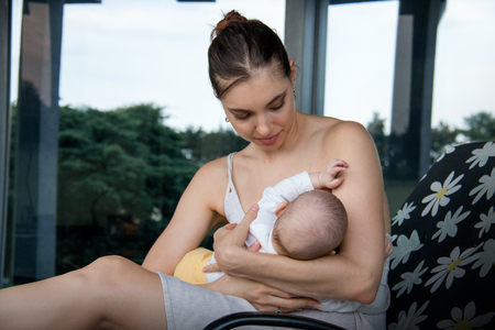 Young caring mother holding a baby and breastfeeding, sitting in dress on flower patter deck chair in front of large grey house window with glass reflection of home garden