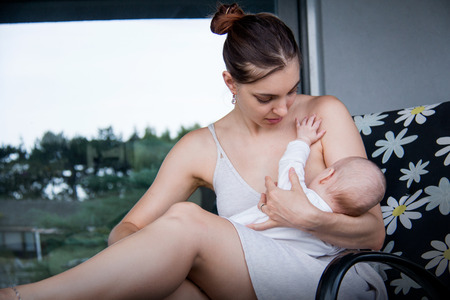 New mom holding her little son and breastfeeding outside, sitting on deck chair house backyard, large mirror windows of the house behind them Stock Photo