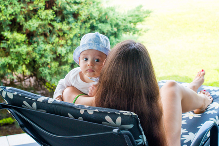 Young lady laying on holiday deck chair and holding her little infant, pretty baby boy wears sun hat and resting on mother's shoulder and looks out with cute expression