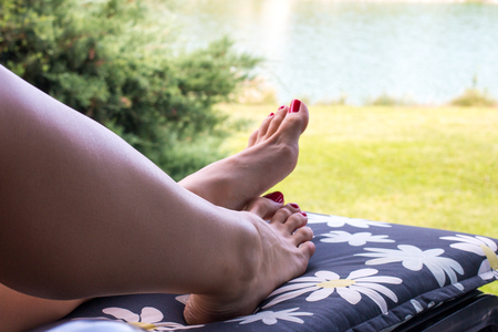 Woman legs with red nails sexy feet lays on the deck chair of flower printed design, holiday concept, girl relaxing barefoot with lake view and green grass on the background