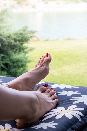 Pretty feet of woman with red nails pedicure on toes relaxing on deck chair outside, view of the lake, grass and nature in background